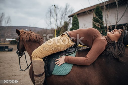 Beautiful young female jockey lying on her horse