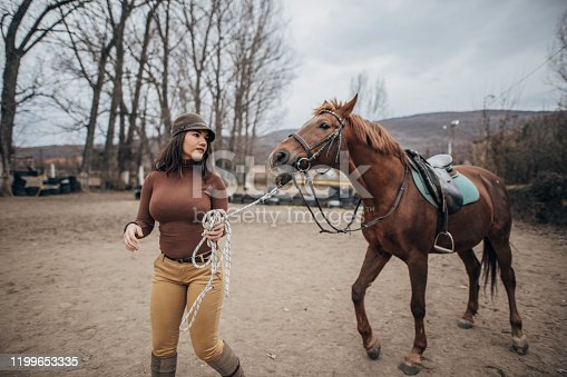 Young female jockey ready to ride her beautiful horse
