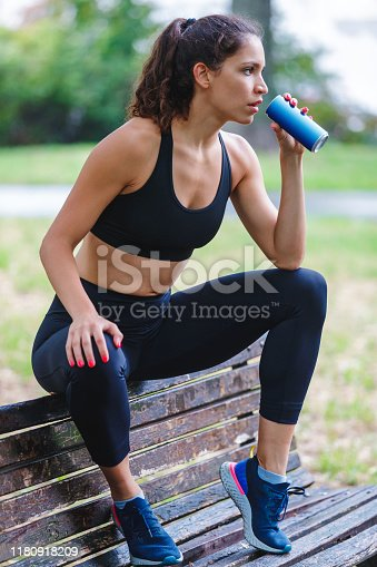 Young woman taking a break from jogging on a park bench and holding a can of drink