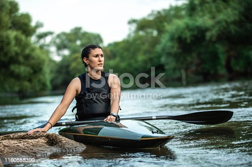 Young attractive female athlete sitting in kayak on river with oar in her hands, looking away