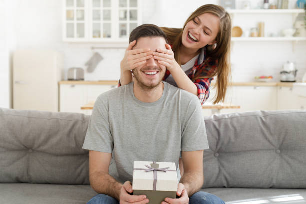 young female keeps eyes closed to his boyfriend at home, while he is sitting on sofa with gift box, celebrating birthday - gift стоковые фото и изображения