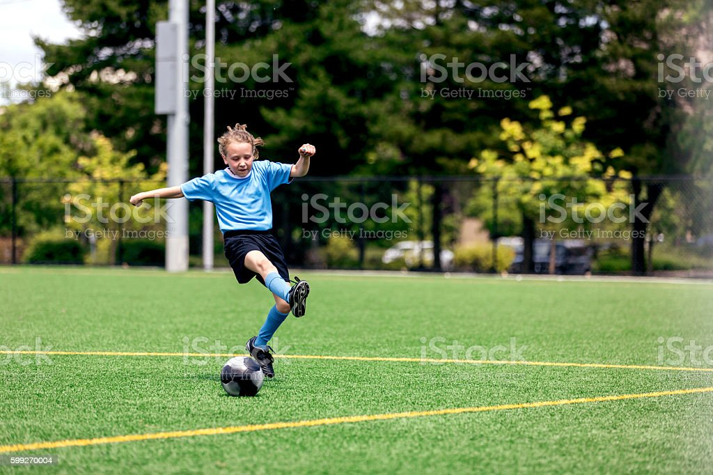 Young female kicking a soccer goal stock photo