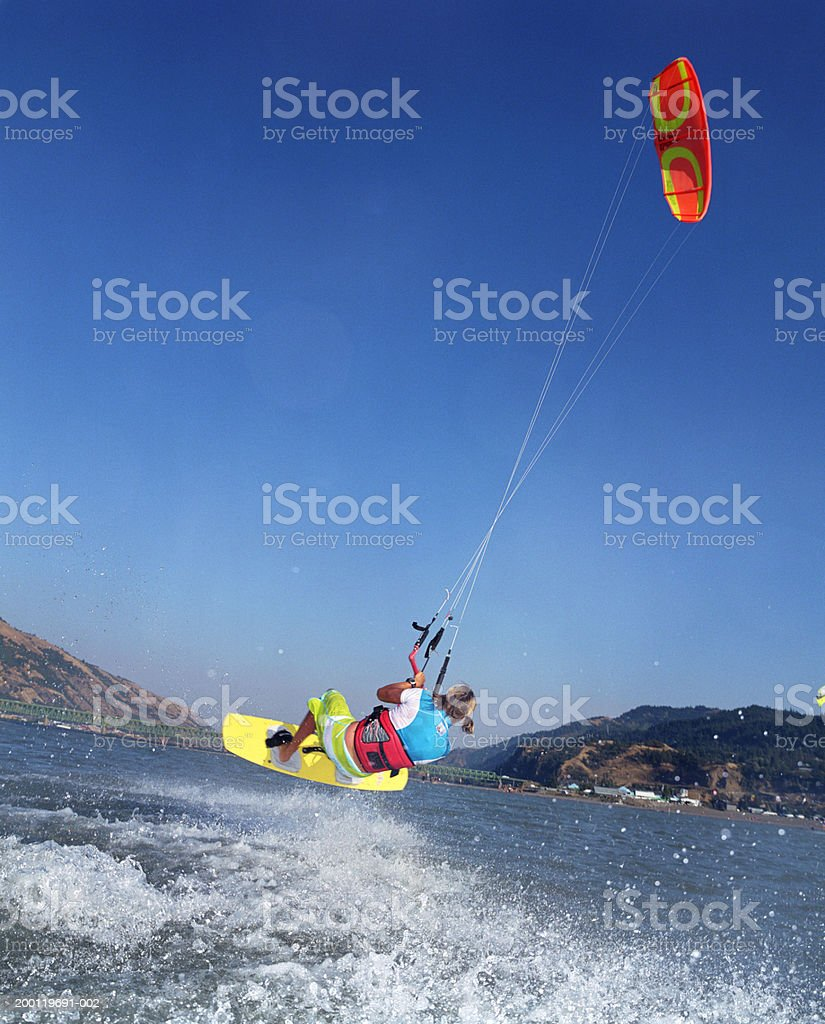 Young female kiteboarder in mid-air, rear view Sandbar on Columbia River at Hood River, Oregon, USA 25-29 Years Stock Photo