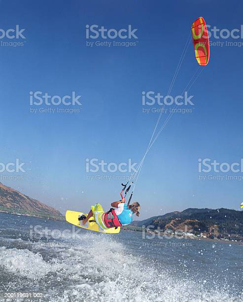 Young Female Kiteboarder In Midair Rear View Stock Photo - Download Image Now