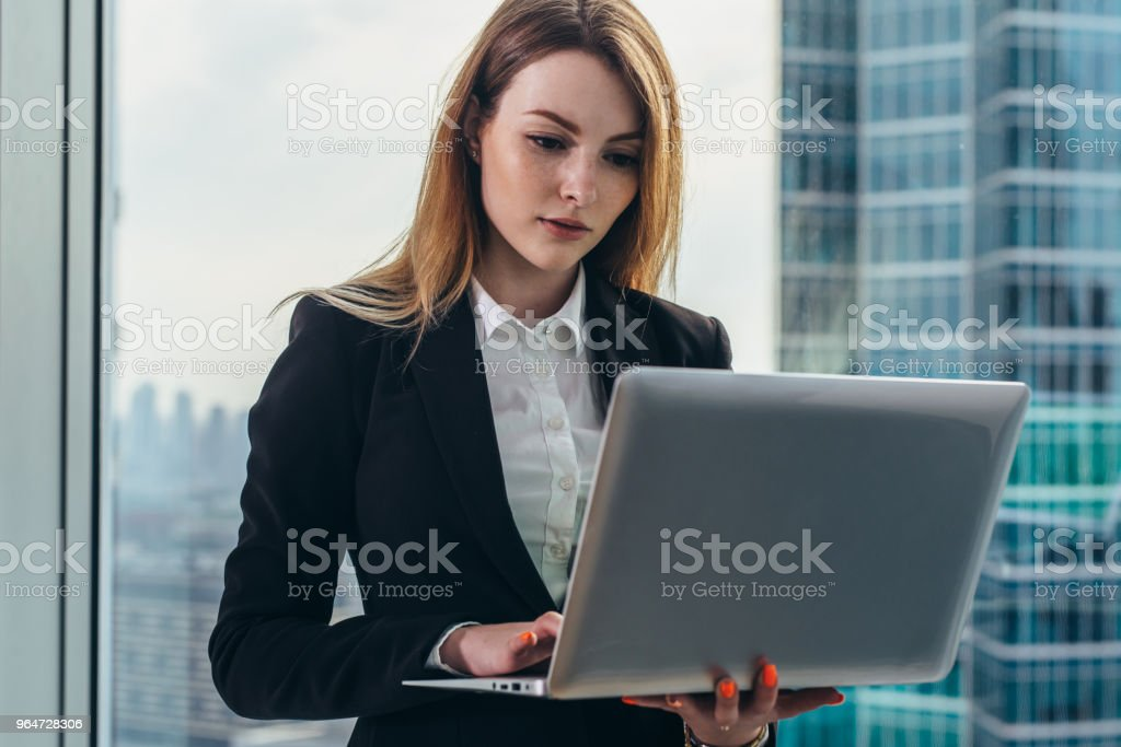 Young female lawyer working in her luxurious office holding a laptop standing against panoramic window with a view on business district royalty-free stock photo