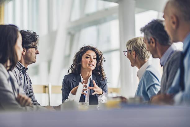 Junge Weibliche Leiterin im Gespräch mit ihren Kollegen bei einem Geschäftstreffen im Büro. – Foto