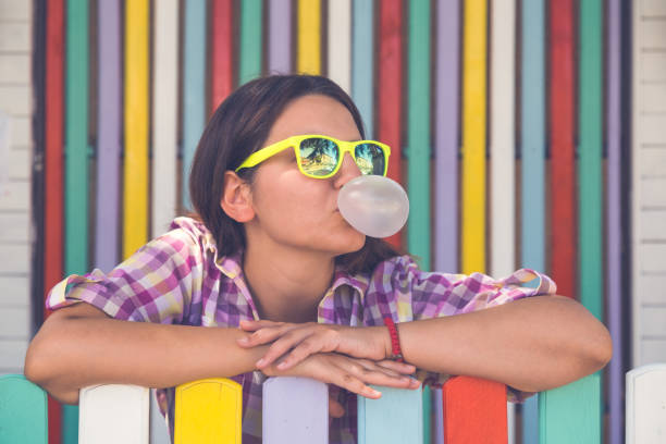 Young female leaning on fence and chewing gum stock photo