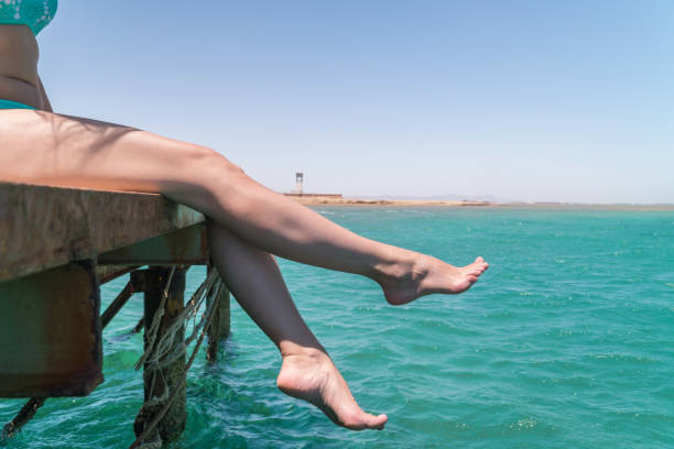 young female legs hang from the pier over the sea water - woman leg beach pov stock photos and pictures