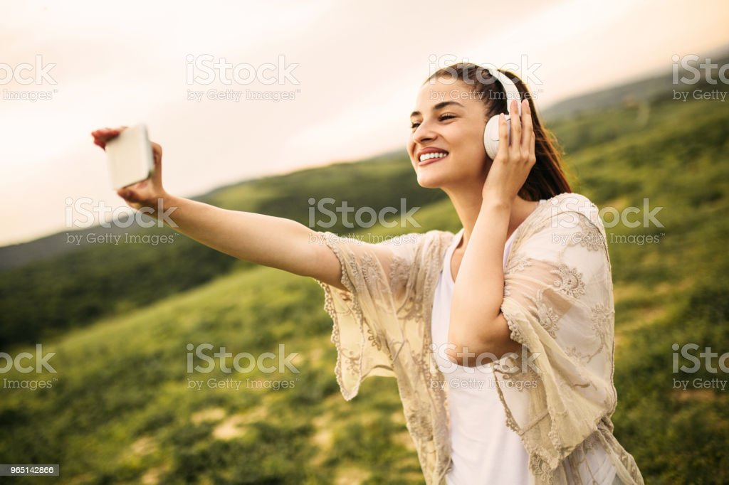 Young female listening music using smartphone zbiór zdjęć royalty-free