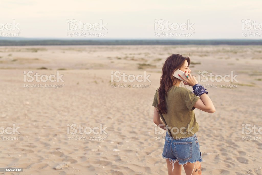Young female lost in desert using mobile phone Young female lost in desert using mobile phone. Woman is looking away while standing on sandy landscape. She is wearing casuals during vacation. 25-29 Years Stock Photo