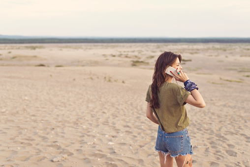 Young Female Lost In Desert Using Mobile Phone Stock Photo - Download Image Now