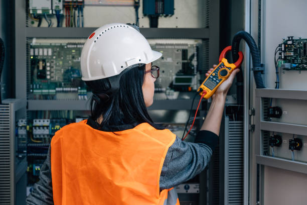 Young female maintenance engineer testing voltage with digital multimeter stock photo