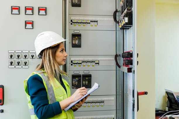 Young female maintenance engineer working at energy control room stock photo