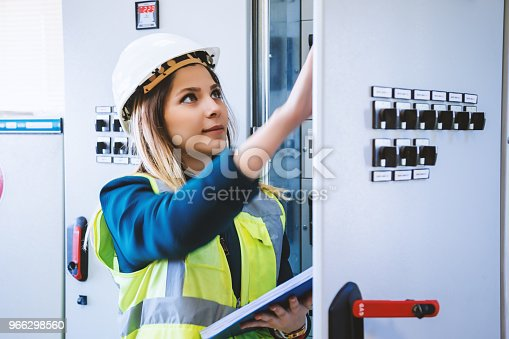 Young woman industrial service engineer wearing white helmet standing, working, checking conducts front of a control panel read and writing notes with digital tablet in energy control room of modern power plant electric energy station. XXXL size taken with Canon 5D MIV