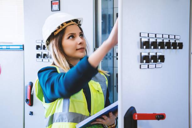 jonge vrouwelijke onderhoud ingenieur werken bij energie controlekamer - elektricien stockfoto's en -beelden