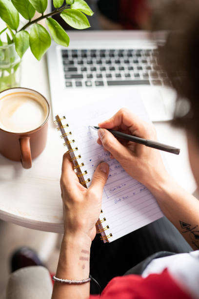Young female manager making notes in notebook while organizing work stock photo