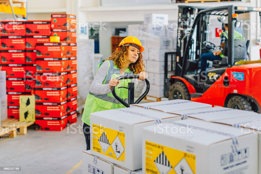 Young female manual worker driving pallet truck in warehouse stock photo