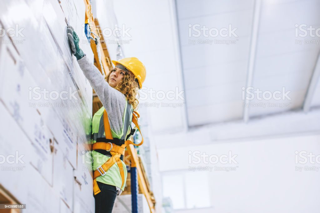 Young female manual worker hanging on a climbing rope in warehouse stock photo
