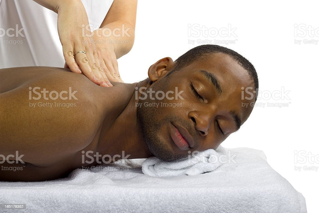 Young female masseuse treating male client with massage royalty-free stock photo
