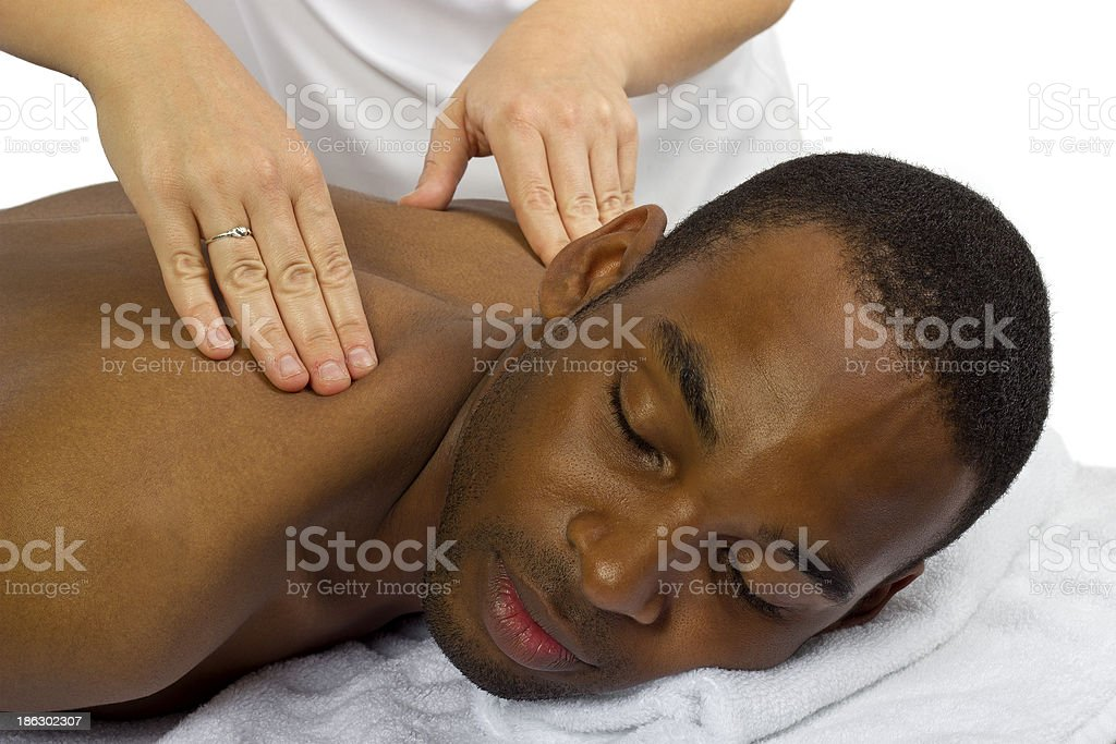 Young Female Masseuse Treating Male Client with Massage stock photo
