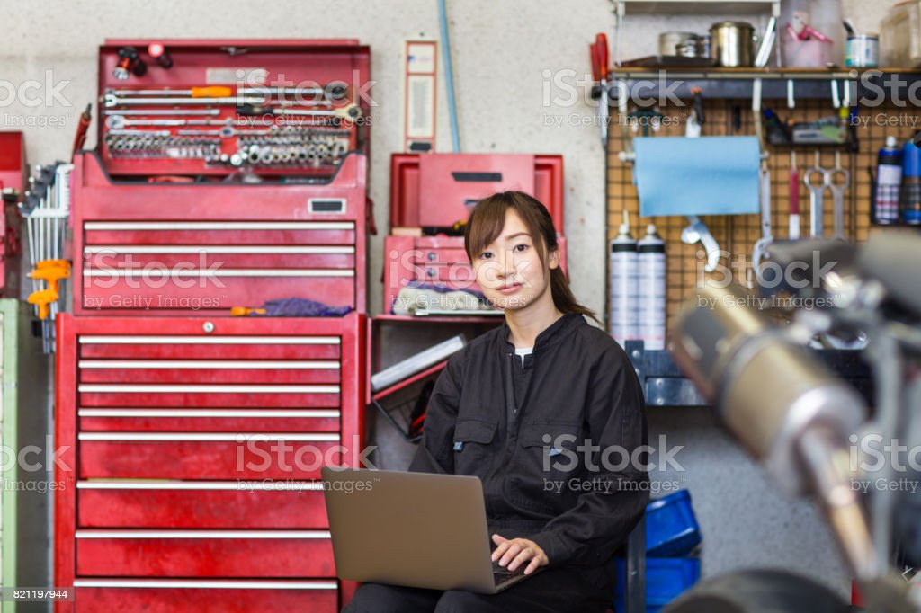 Young female mechanic repairing a motorcycle in her small business garage. stock photo