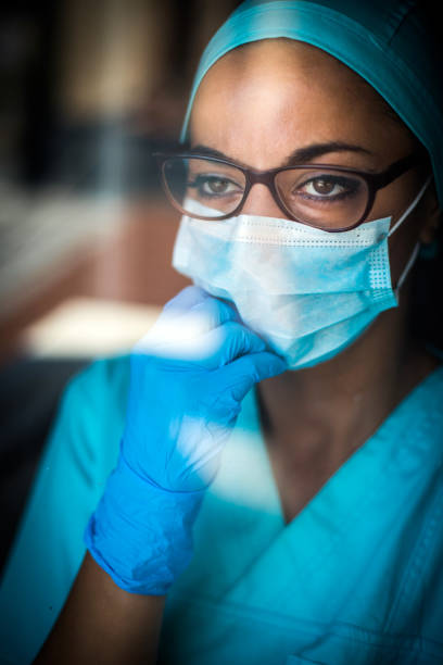 Young female medic, wearing a mask and glasses stock photo