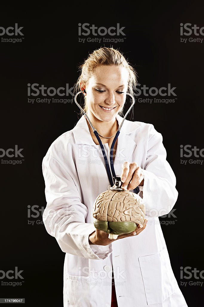 Young female medical professional listens to model brain with stethoscope stock photo