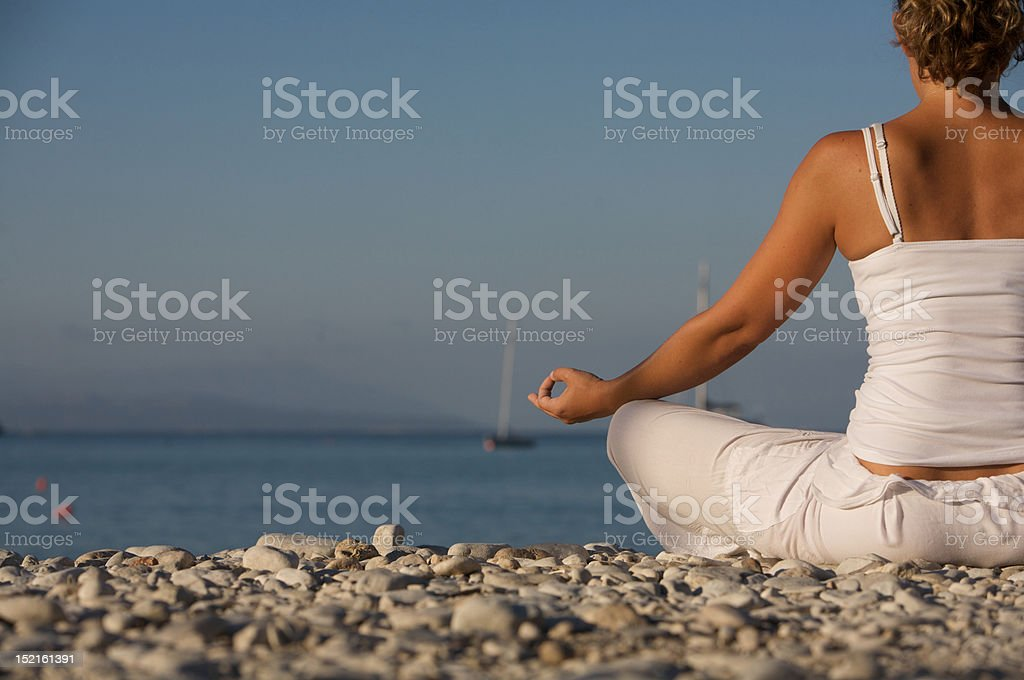 Young female meditating on Beach royalty-free stock photo