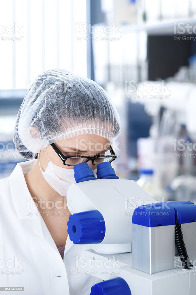 Young female microscopist looking through a microscope royalty-free stock photo