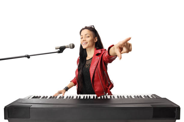 Young female musician playing a digital piano, singing on a microphone and pointing Young female musician playing a digital piano, singing on a microphone and pointing isolated on white background keyboard player stock pictures, royalty-free photos & images