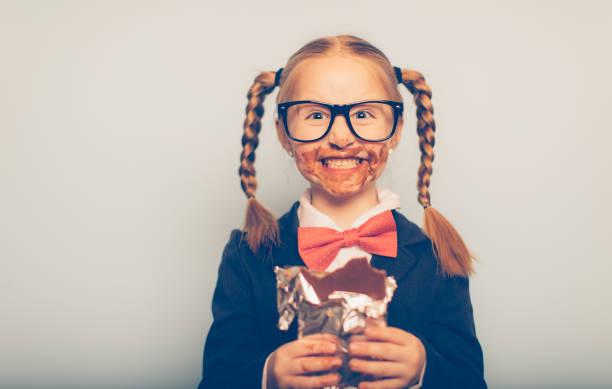 young female nerd eating chocolate bar - kinderschokolade stock-fotos und bilder