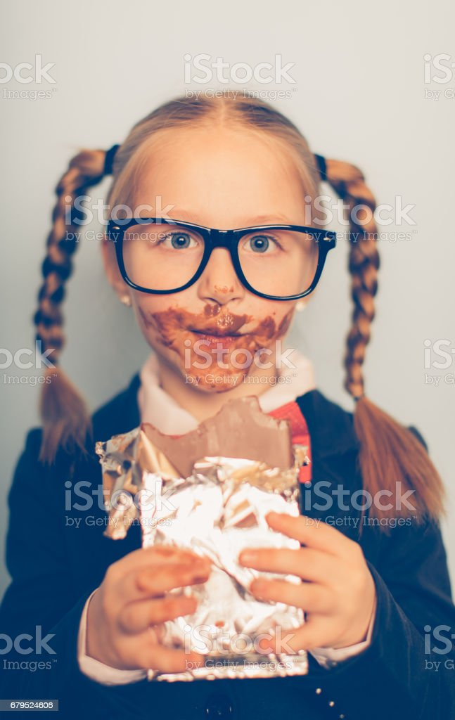 Young Female Nerd Eating Chocolate Bar royalty-free stock photo