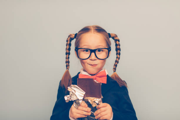 Young Female Nerd Eats Chocolate Bar A young girl nerd is eating a chocolate bar a bit too big for her. She is dressed in a blue cardigan and pink bow tie. She is enjoying that chocolate bar very much. nerd hairstyles for girls stock pictures, royalty-free photos & images