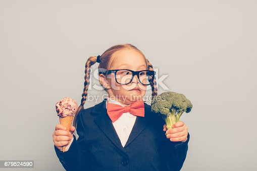 A young female nerd dressed in bow tie and eyeglasses is deciding between eating an ice cream cone or broccoli. She is making a disgusted face at the broccoli. She is choosing the treat.