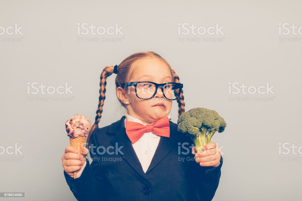 Young Female Nerd Holds Ice Cream and Broccoli stock photo