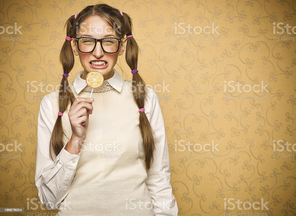 Young female nerd with lollypop royalty-free stock photo