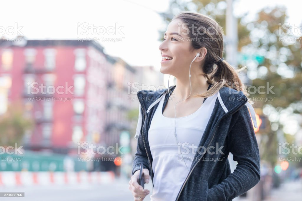 Attractive young Caucasian woman holds a smart phone and is wearing...