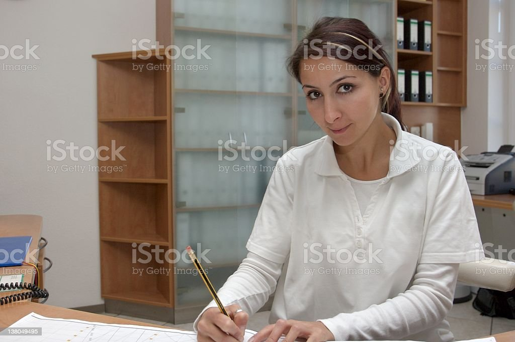 young female nurse doing paperwork, looks into camera royalty-free stock photo