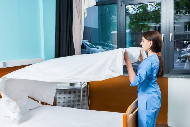 junge krankenschwester in blauen workwear-ändern bettwäsche von krankenhausbett - verwandlungskissen stock-fotos und bilder