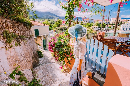 istock Young female on summer vacation in Greece looking towards wonderful summer day. Cute woman leaving the house and exploring the town. Travel vacation, lifestyle carefree joy and happiness concept 1093611740