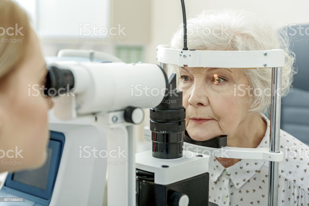 Young female ophthalmologist using apparatus stock photo