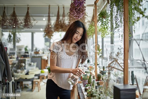 Confident female owner watering potted plants in store. Young woman is gardening in greenhouse. She is wearing casuals.