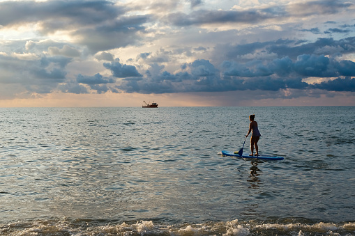 Young female paddling on SUP board in the sea at amazing dark sunset and waves.