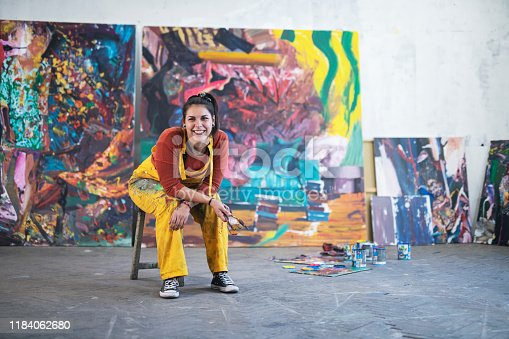Smiling portrait on young female artist, she sitting in front of her big paintings and looking at camera.