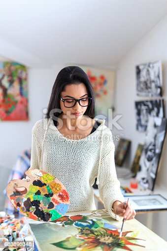 istock Young female painter drawing flowers in atelier 683895348