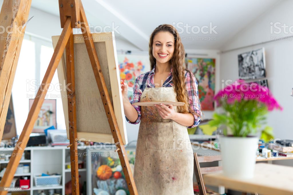 Young female painter drawing flowers in atelier royalty-free stock photo