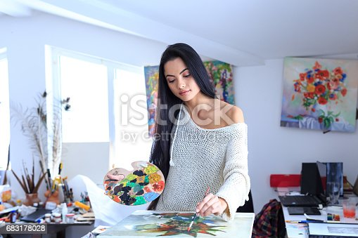 istock Young female painter drawing in atelier 683178028