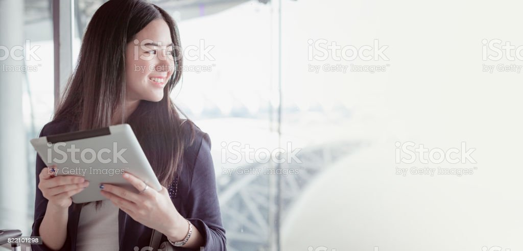 Young female passenger at the airport, using her tablet computer while waiting for her flight stock photo