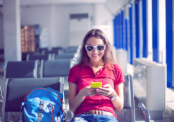 Young female passenger on smart phone at airport stock photo