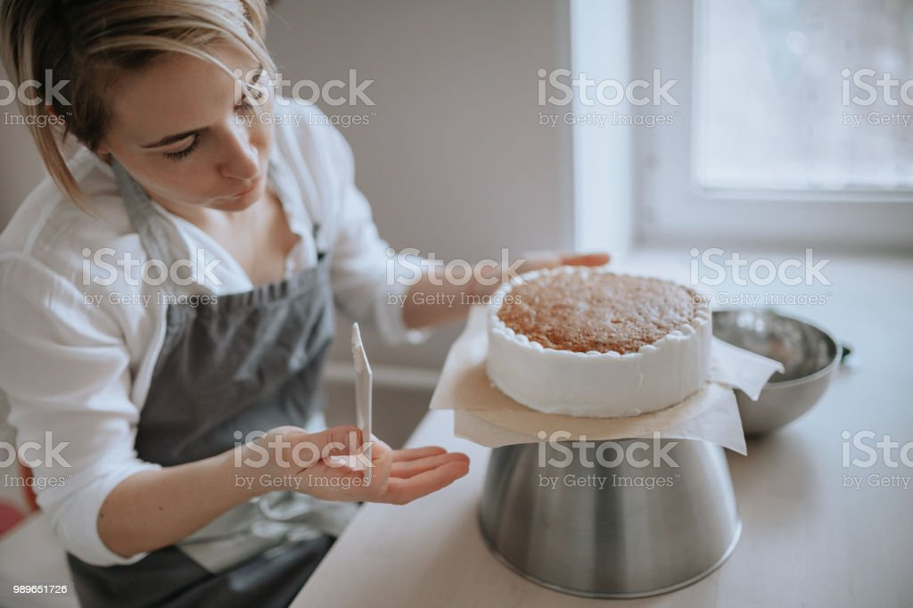 Young female pastry chef or a baker preparing a cake. A young woman confectioner or baker prepares a cake and decorates it with icing. Adult Stock Photo